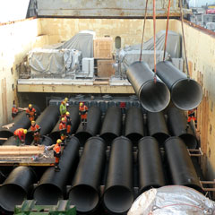 Loading of ductile pipes into ship's hold.